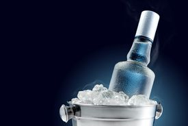 Bottle of cold vodka in bucket of ice.