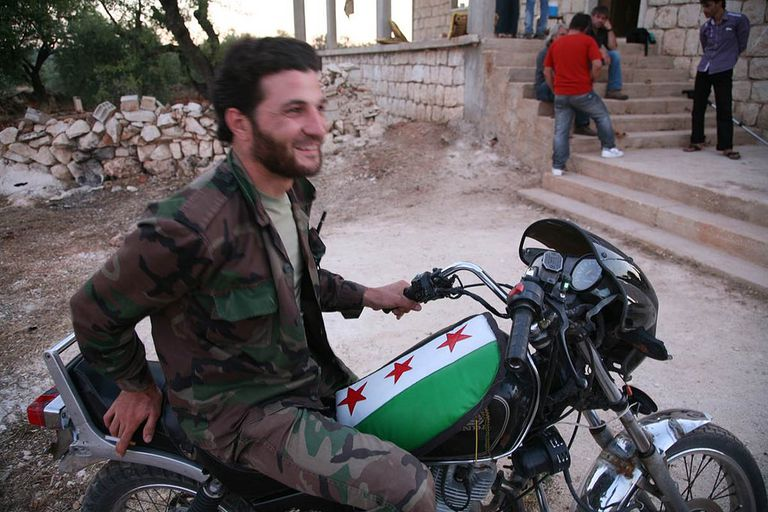 Rebel Commander Ahmad Bakran sits on his rebel flag-adorned motorcycle in the village of Mghara, Syria