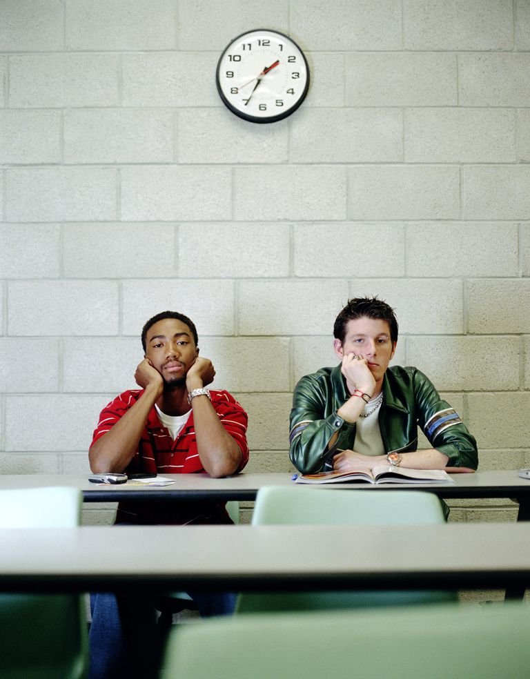 Students sitting together under a clock in back of class.