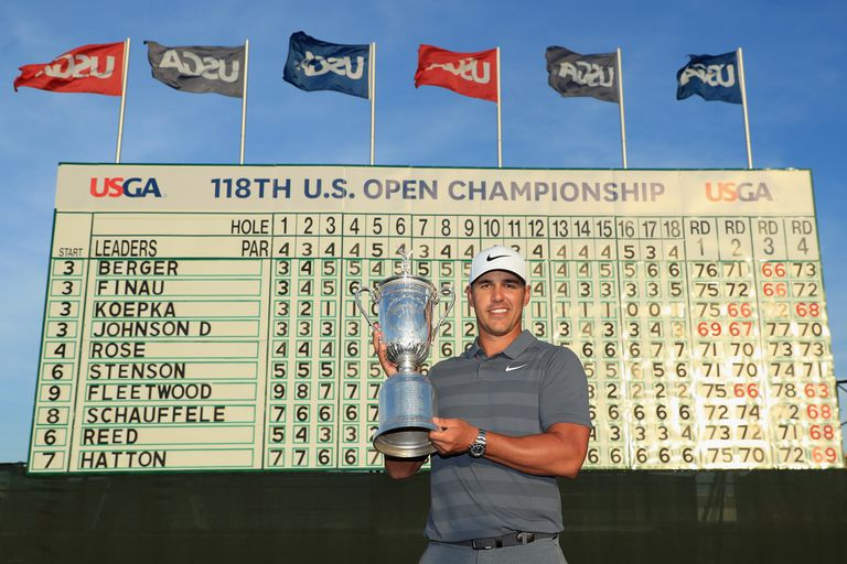 Brooks Koepka displays the trophy after winning the 2018 U.S. Open golf tournament.