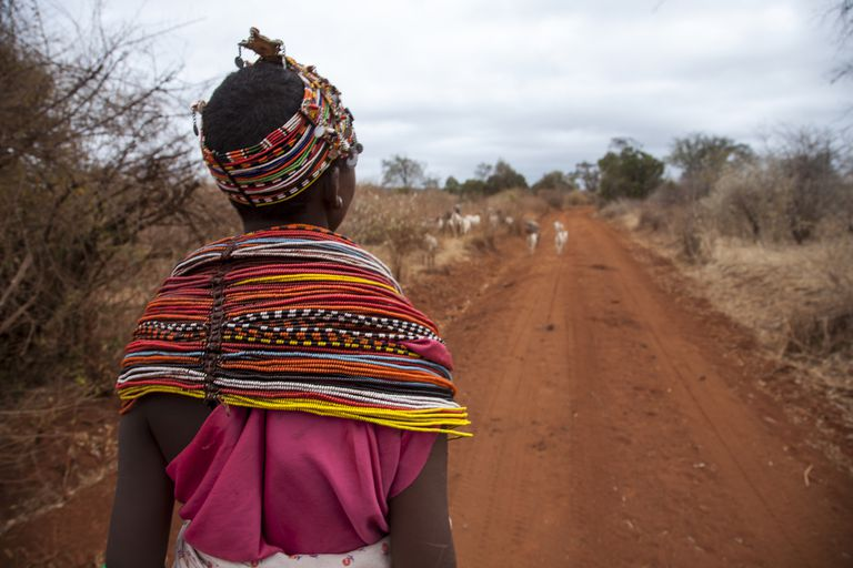 Kenyan woman in traditional garb walking along dirt road.