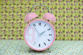 pink alarm clock in vintage background