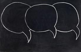 A set of speech bubbles on a blackboard