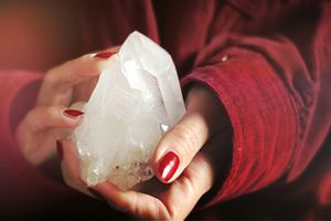 Female hands holding a large crystal close up.