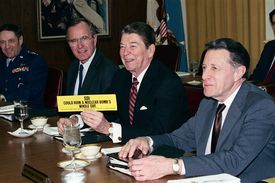 President Reagan Holding Up Bumper Sticker During Meeting