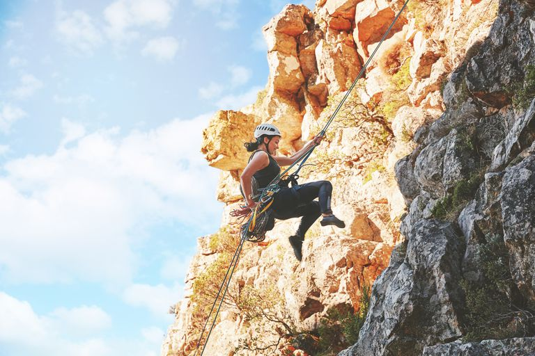 Woman rock climber descending rocks