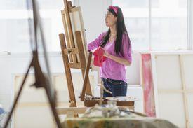 Mixed race teenage girl painting in studio