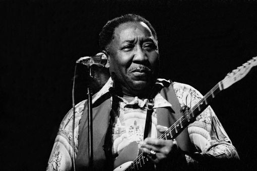 Muddy Waters plays guitar in a performance