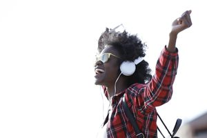Happy young woman listening music with headphones and cell phone