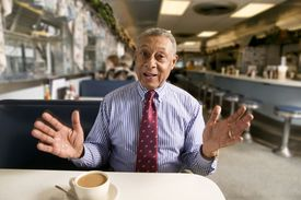 senior man talking with hands telling a story in diner