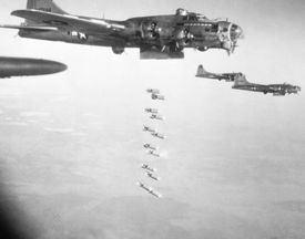 WWII planes dropping bombs over a city.