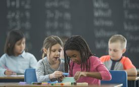 Kids in math class use stackable blocks for simple math
