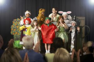 Children (4-9) Wearing Costumes and Teacher Waving on Stage