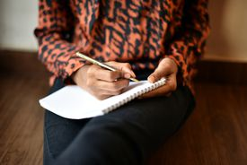 Close up of a woman writing on a notepad with a pen
