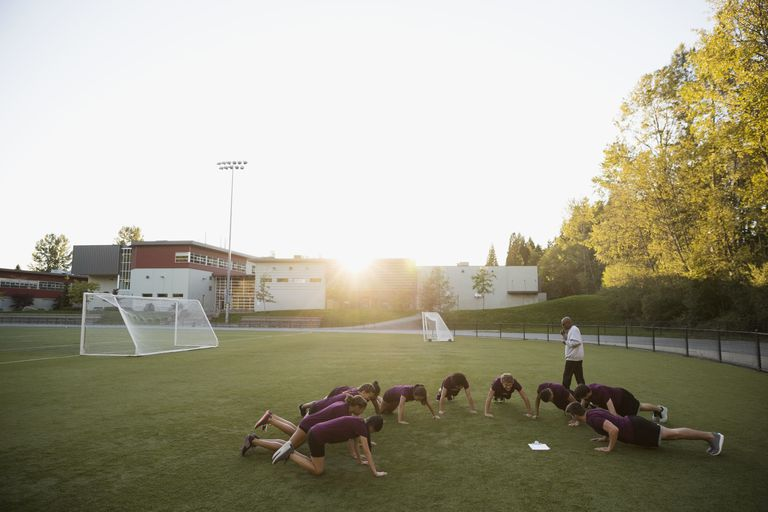 High school students doing push-ups physical education