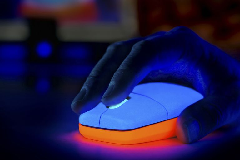Person using a glowing computer mouse