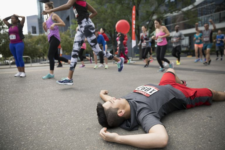 Exhausted male marathon runner collapsing at finish line
