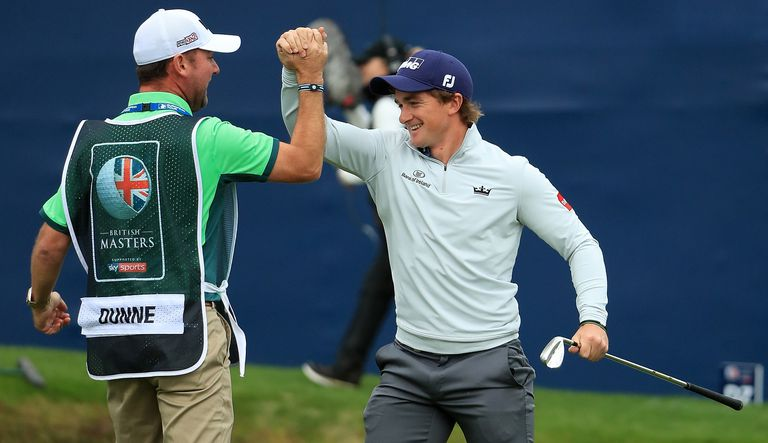 Paul Dunne celebrates with caddie Darren Reynolds after chipping in on the final green at the 2017 British Masters tournament.
