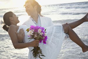 Bridal couple near Tulum, Mexico on the beach with the sun and water in the background.