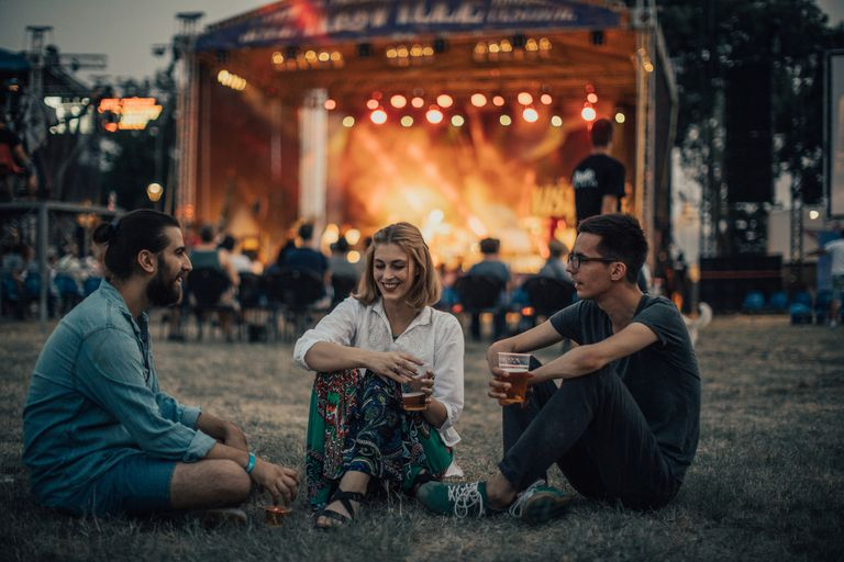 Friends sitting outside a concert crowd.