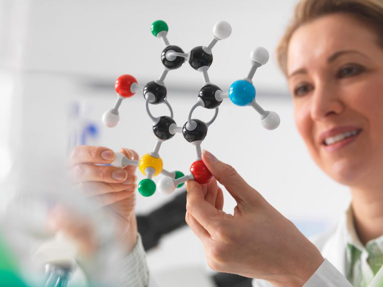 Woman examining plastic model of a molecule