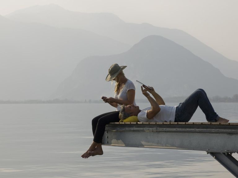 A couple lazing on a jetty above a lake
