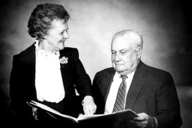 Elderly grandparents peruse a family album together