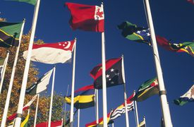 Flags of countries belonging to the Commonwealth of Nations against a blue sky.