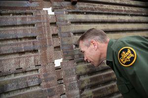 U.S. Border Patrol agent Jerry Conlin peer through the U.S.-Mexico border fence
