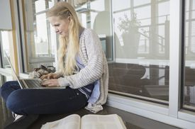 High school student using laptop on floor