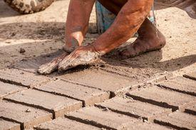 Close up of muddy hands forming adobe bricks