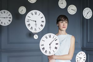 a woman surrounded by floating clocks