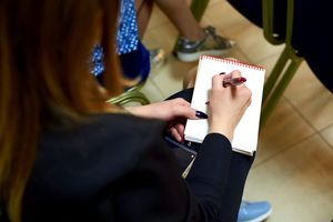 A journalist takes notes by hand in her notepad