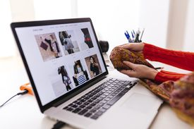 Woman holding fabric in front of a laptop with a fashion website open