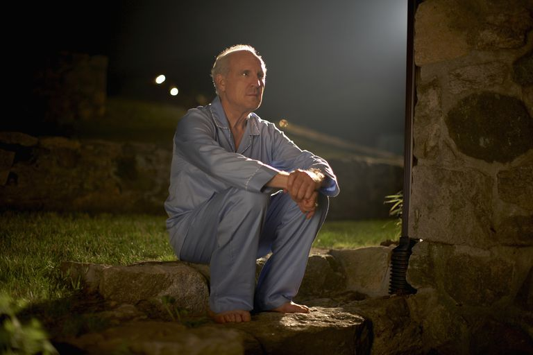 Senior man in pyjamas sitting outside house at night
