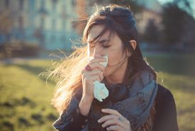 woman blowing nose with hankerchief in park