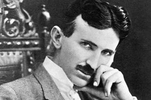 Photograph of Nikola Tesla, a slender, moustachioed man with a thin face and pointed chin.