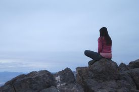 Girl sitting on a rock contemplating life's big questions