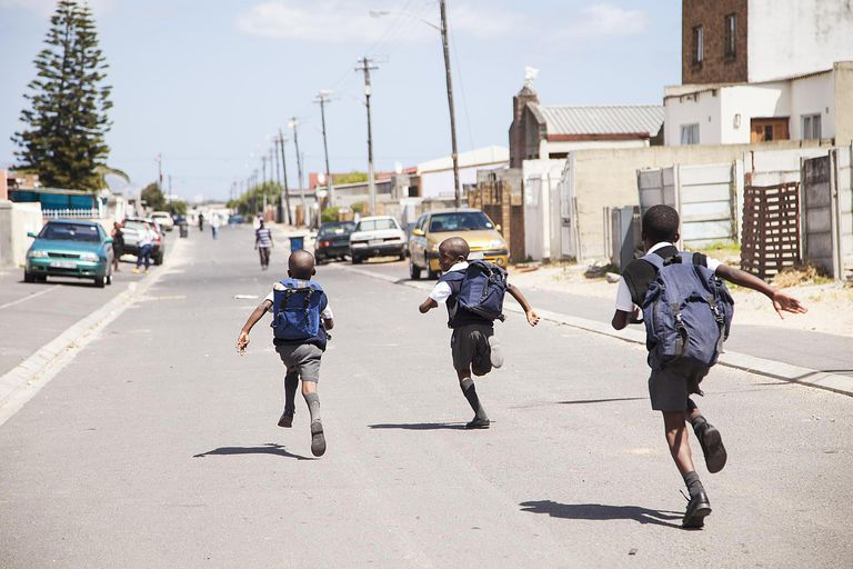 Three young boys running down the street, Cape Town, South Africa
