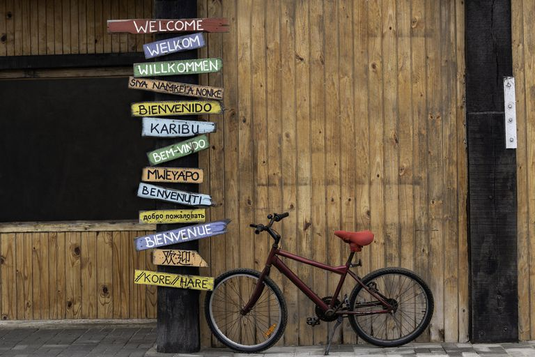 Red Bike Next to Welcome Signs in different languages