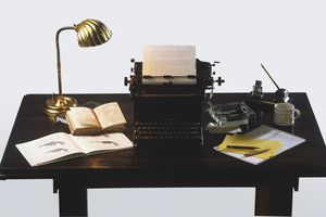 Golden desk lamp, open books, old-fashioned typewriter and writer's equipment on wooden desk.