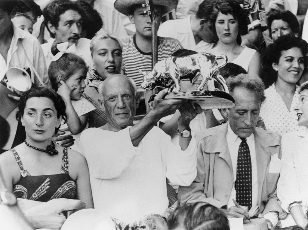 Jacqueline Roque and Picasso stand among a crowd, while Picasso holds aloft a statue of a bull