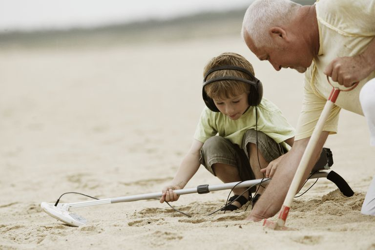 A man and child use metal detector on the beach