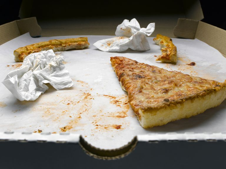 The remains of take-out: cold slice of pizza, half-eaten crusts, and used napkins in a pizza box