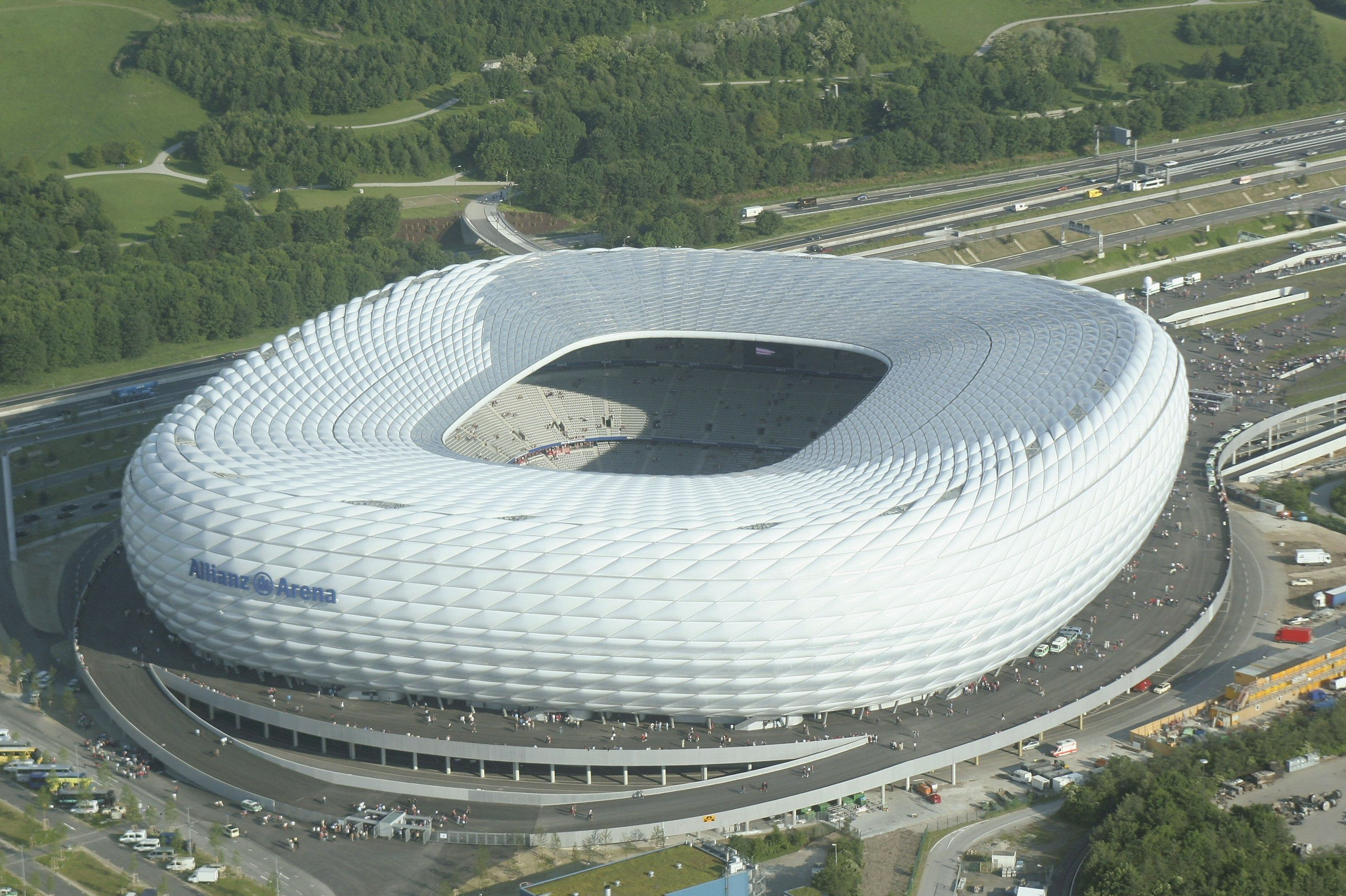 Aerial View of large, rounded square stadium, sculpted white, Allianz Arena signage, open air center