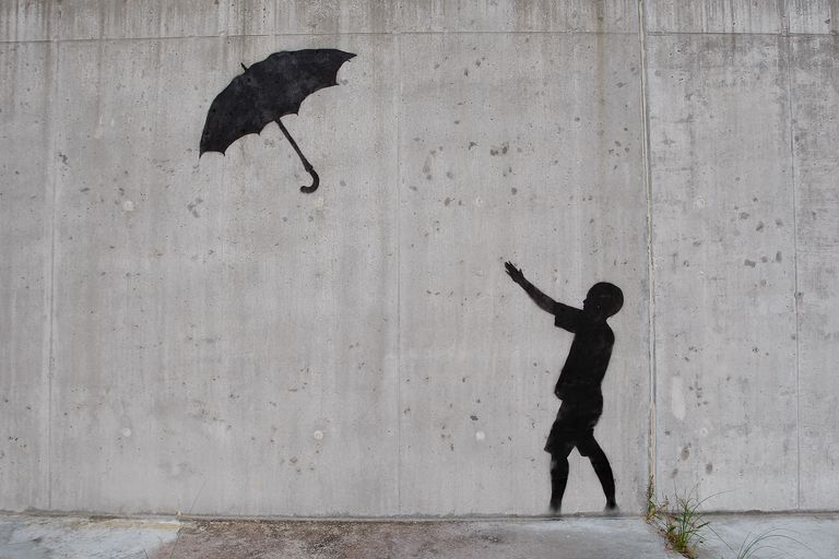 concrete wall illustrated with black silhouette of person reaching for an unbrella blowing away