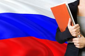 Learning Russian language concept. Young woman standing with the Russia flag in the background. Teacher holding books, orange blank book cover.