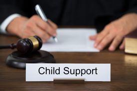 judge behind child support desk sign