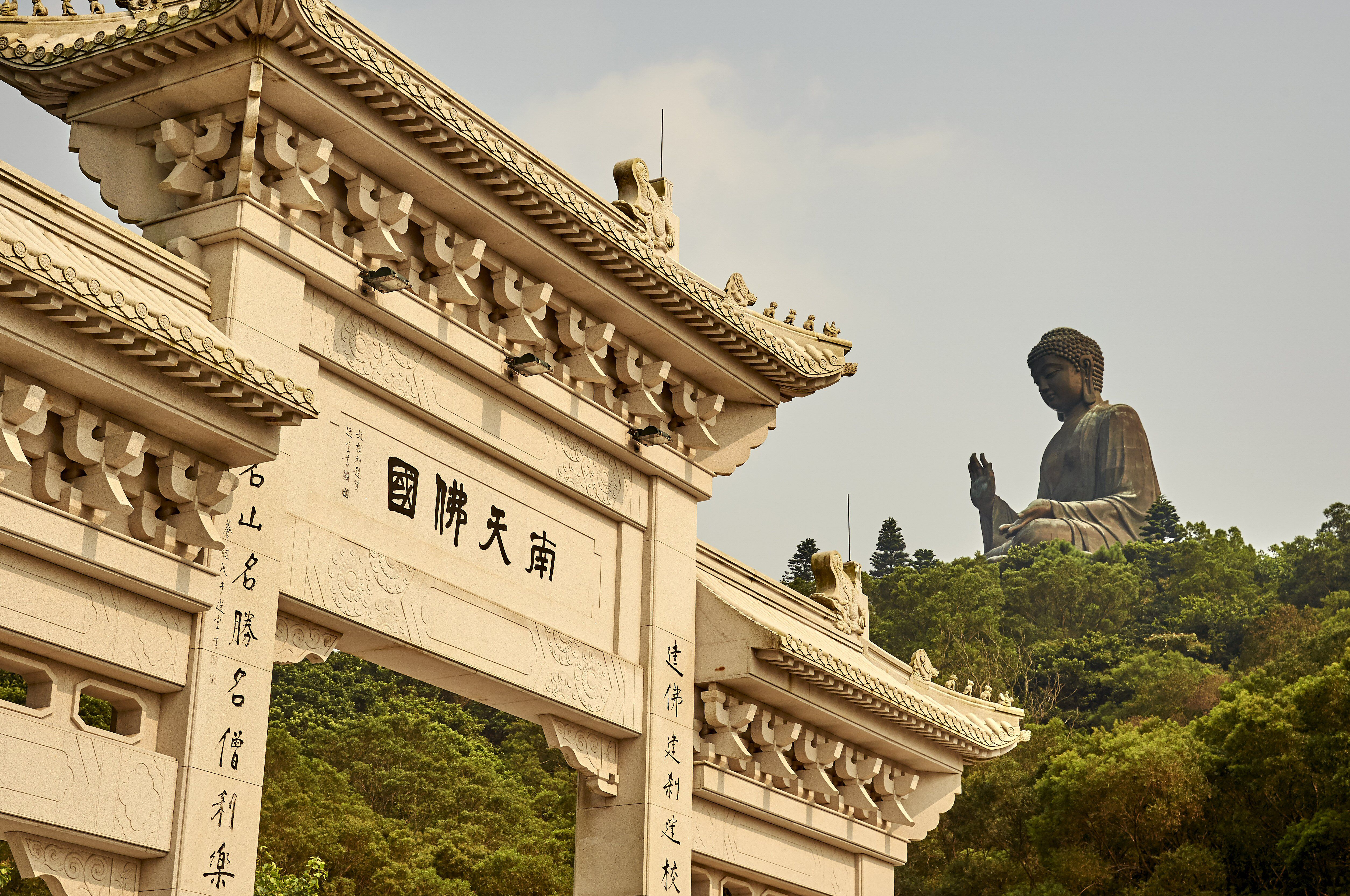 Chinese entrance in foreground and huge statue in background
