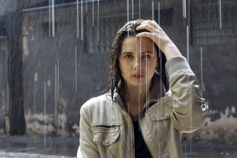 Young woman standing in the rain looking at camera with a fixed stare.